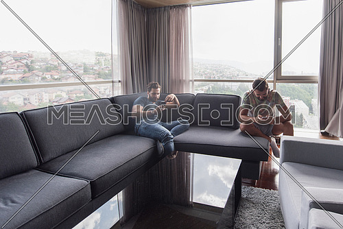 Handsome casual young men using a mobile phones  near the window at home
