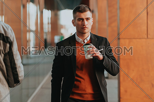 Portrait of tourist man carrying a suitcase and holding a cup of coffee while walking outdoors on the street. Tourism concept.