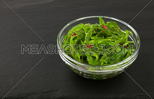 Close up portion of green wakame seaweed salad in glass bowl over black slate board background, elevated top view, directly above