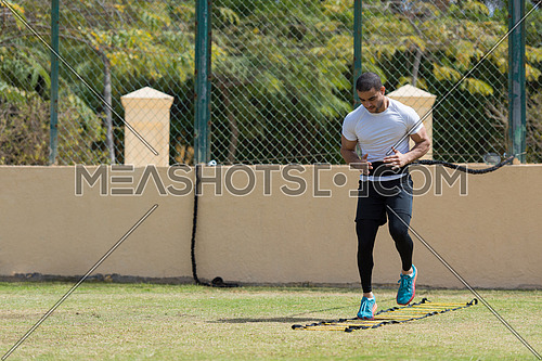 young middle eastern man athlete running and exercise to speed ladder out in the field on a sunny day