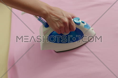 Close and Follow Shot for A female hand Ironing pink Shirt