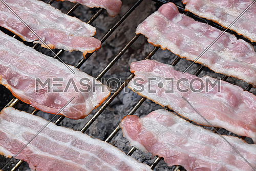 Raw smoked melting grilled barbecue bacon slices, being cooked on bbq smoke grill, close up