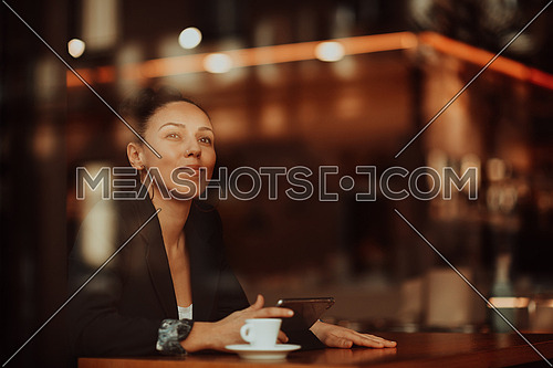 a businesswoman sitting in a cafe on a break and using a tablet