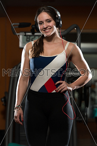 Cute Girl With Headphones Relaxing In The Gym