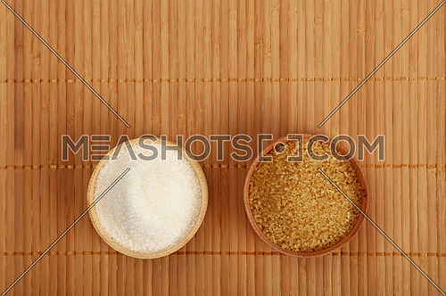Choice, selection of two sugars in small wooden bowls on bamboo mat background, brown cane and white sugar, top view