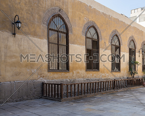 Row of three adjacent wooden grunge arched window with decorated wrought iron grid over yellow stone bricks wall and wooden balustrade, Medieval Cairo, Egypt
