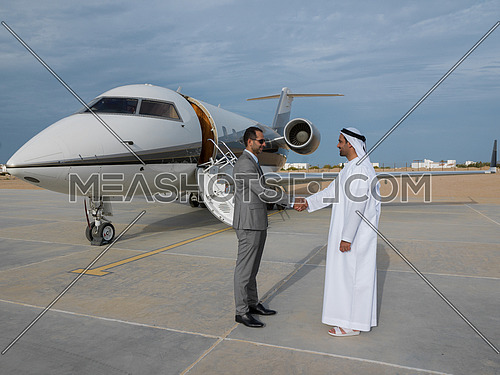 Young successful businessman shake hands with their Arab business partner in front of the private airplane