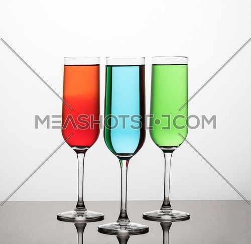 Three glasses filled with colored water on bright background