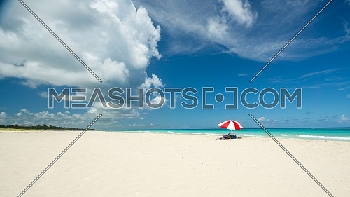 Awesome beach of Varadero during a sunny day, fine white sand and turquoise and green Caribbean sea,on the right one red parasol,Cuba.concept photo,copy space.
