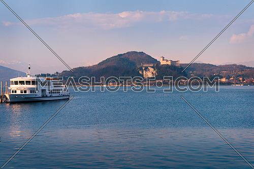 In the picture boat moored at the port of Arona, Maggiore Lake and in the background the fortress of Angera.