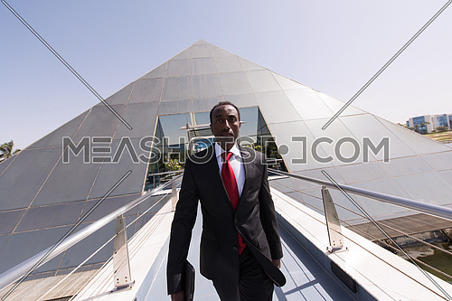 african businessman walking across modern footbridge