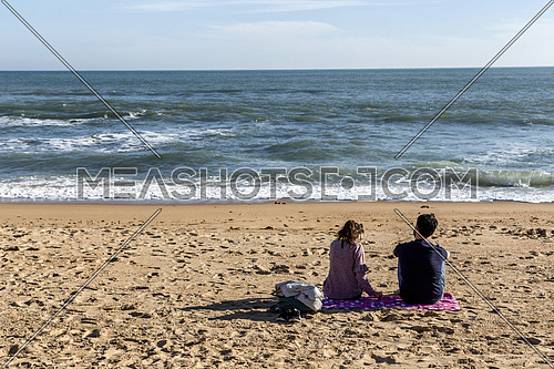 Rear view of couple sitting on the beach in Caleta beach, Cadiz, Andalusia, Spain