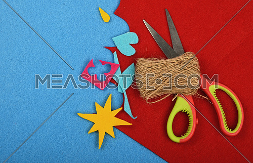 Craft and art, felt pieces, cuts, jute twine thread bobbin and scissors on red and blue background