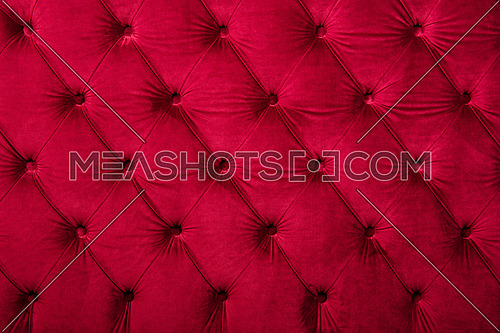 Red burgundy velvet capitone textile background, retro Chesterfield style checkered soft tufted fabric furniture diamond pattern decoration with buttons, close up