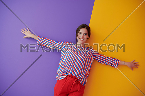 Young female model with open wide arms posing over purple and yellow background. Girl in modern fashionable clothes leaning against wall in the studio with stretched hands. Freedom