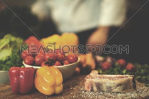 Juicy slice of raw steak  with vegetables around on a wooden table