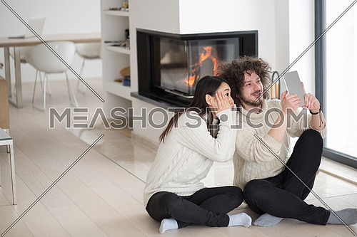 beautiful young multiethnic couple using tablet computer in front of fireplace on cold winter day at home