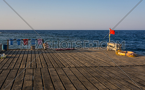 Red flag for warning lifebelt and colors baskets carry objects on a  old wooden pier for diving and snorkeling at sunset.copy space.