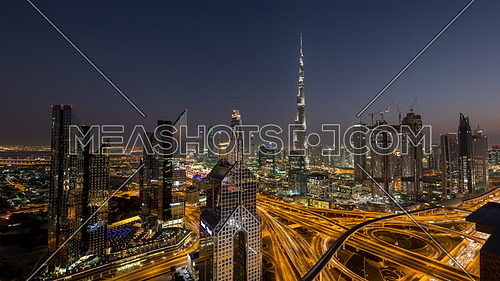 Extreme long shot for Dubai City showing Burj Khalifa and skyscrapers and traffic from day to night