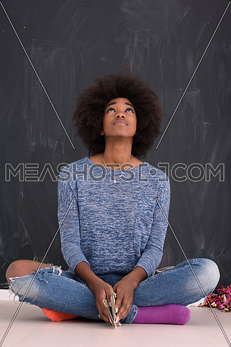 portrait of a beautiful friendly African American woman with a curly afro hairstyle and lovely smile sitting isolated on a gray background