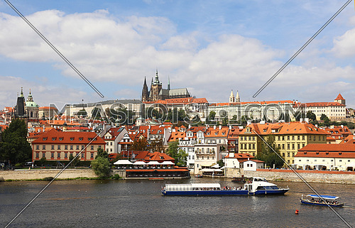 View of Prague lesser old town with Royal castle palace and Saint Vitus Cathedral over Vltava river and blue sky