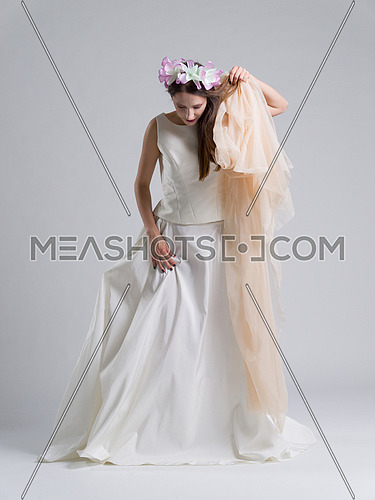 Portrait of beautiful young bride in a wedding dress with a veil isolated on a white background