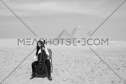 black and white shot of young female cello player in egyptian desert with pyramids in background