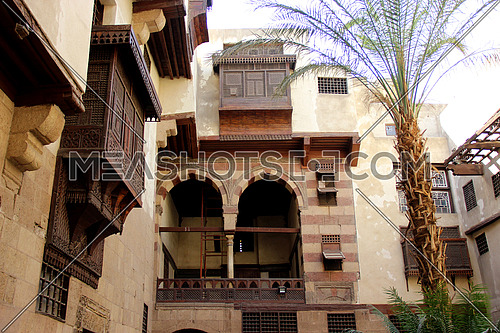 a photo for an ancient Islamic house in old Cairo, Egypt showing the architecture style used at that time and the wooden windows style