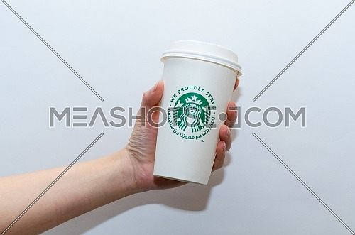 A female holding the traditional paper cup of Starbucks coffee cup with Arabic writing saying ( We Proudly Serve Our Coffee from Starbucks) on a white