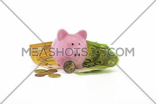 Euro banknotes and loose coins with a little ceramic pink piggy bank over a white background with copyspace for savings, finances or money related themes