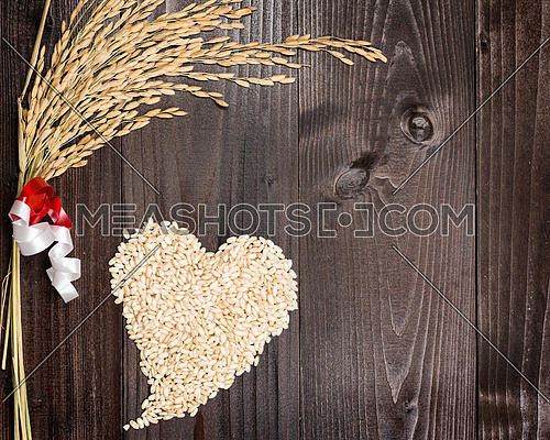 In the picture an ear of wheat and a heart formed by grains of rice on background of wood