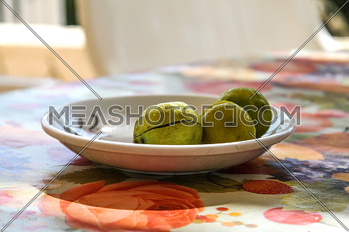 Three lemons in a white plate