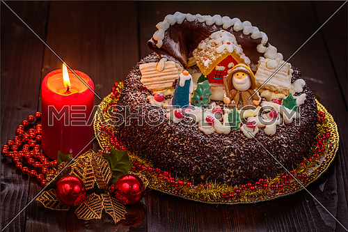 Chocolate cake decorated for christmas with candle  on wooden table.
