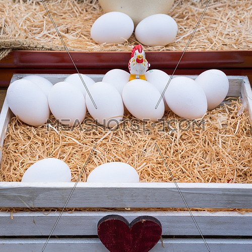 White chicken eggs leaning on straw in wooden basket
