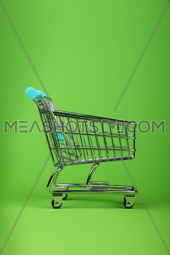 Close up empty toy metal supermarket shopping cart over pastel green background with copy space, low angle side view