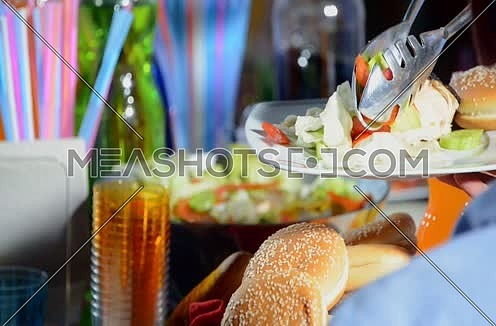 female hands putting salad in a plate during family dinner