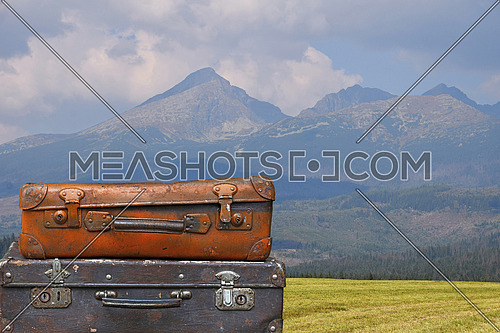 Stack of two old vintage antique grunge travel luggage brown leather suitcase trunks over background of mountain landscape, close up, low angle side view