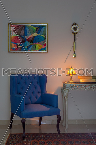 Vintage Furniture: Interior composition of blue armchair, vintage wooden beige table, illuminated table lamp, books, pendulum clock and orange ornate carpet, with clipping path for the hanged painting