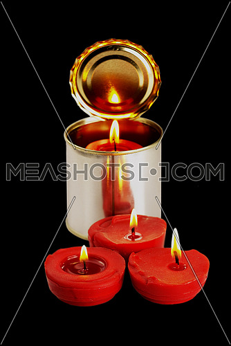 red candle on a tin can over black background