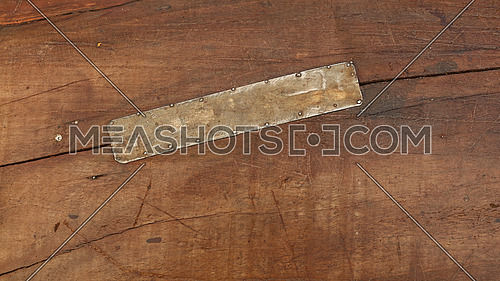 Grunge background texture of brown wood with dirty stains, scratches, cracks and nailed tin metal patch, close up