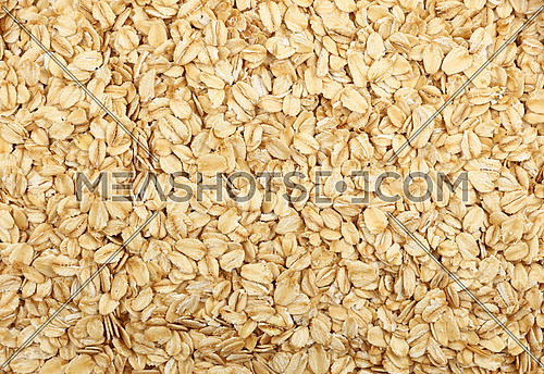 Flakes of porridge oat grits for oatmeal close up pattern background, elevated top view