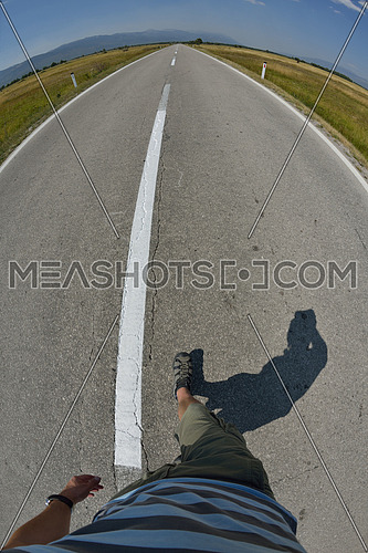 pov view of man walking in alone on country road at sunny summer day
