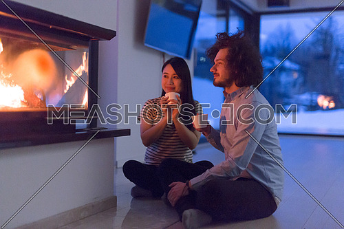 Young romantic multiethnic couple sitting on the floor in front of fireplace at home, talking and drinking tea on cold winter night