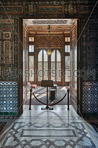 Manial Palace of Prince Mohammed Ali. Entrance of a small room at reception hall with ornate wooden wall and ceiling, decorated wooden windows, lantern and ornate marble floor, Cairo, Egypt