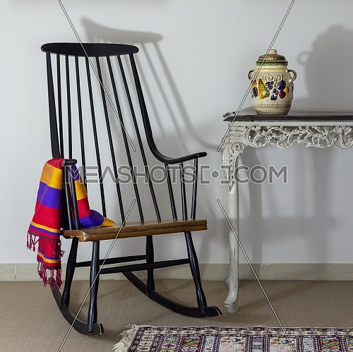 Classic rocking chair and old style vintage table on background of off white wall