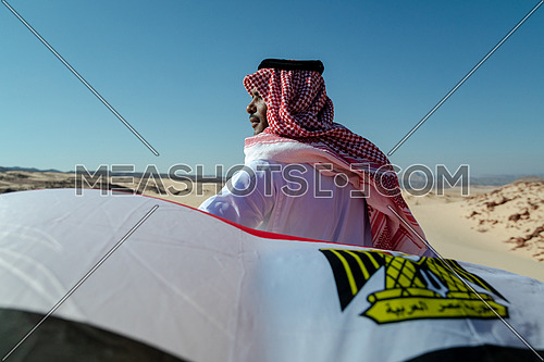 Bedouin man holding Egyptian Flag in Sinai Trail from Ain Hodouda by day.