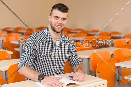 Portrait Of Young Male College Student With Book Sitting In Classroom Alone
