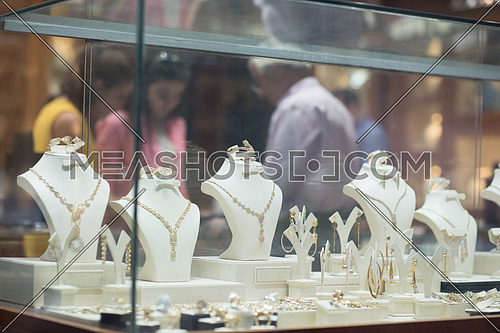 two young happy middle eastern women enjoy trying out jewelry in a luxury jewelry store