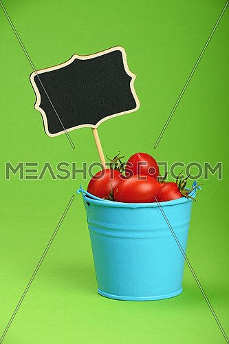 Small disproportional blue bucket of red cherry tomatoes and black chalkboard sign over green background, close up