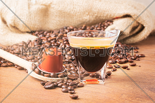 Cup of coffee with coffee capsule on wooden spoon, roasted coffee beans on wooden background,front view.